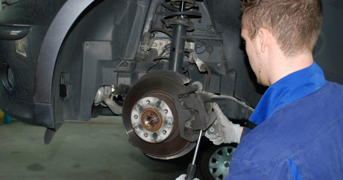 Mechaniker beim Auswechseln der Bremsbeläge