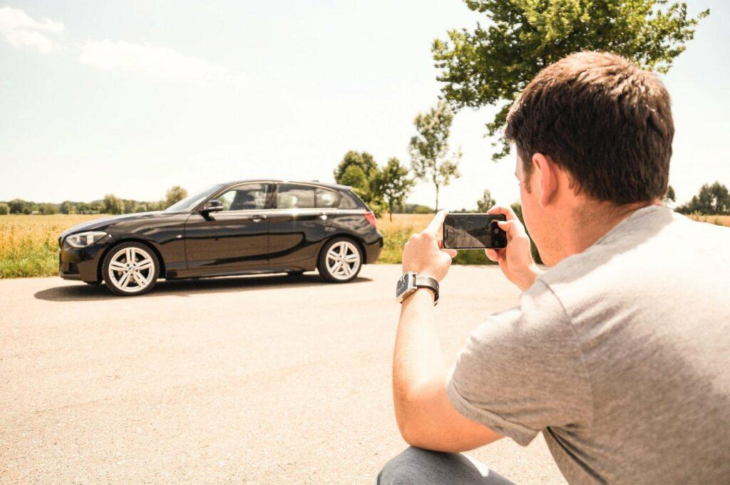 Mann fotografiert Auto mit dem Handy