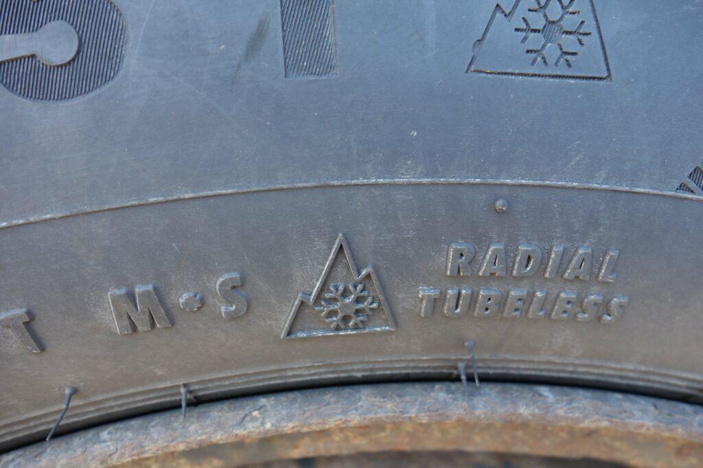 Schneeflockensymbol und M+S-Kennzeichung auf Reifen dargestellt