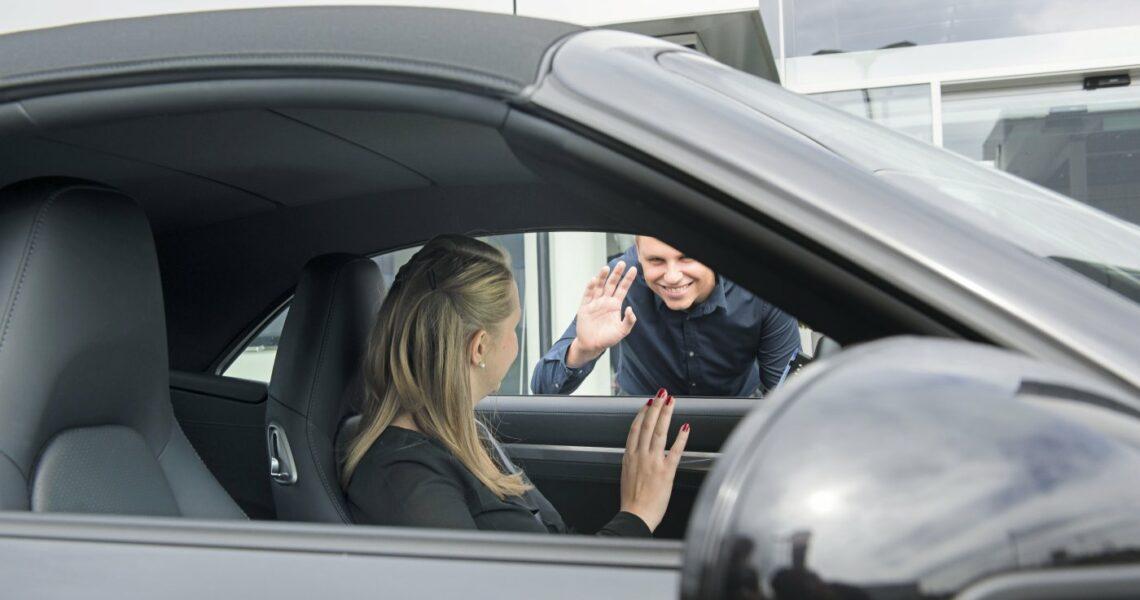 Potenzielle Käuferin im Auto und Verkäufer am Auto