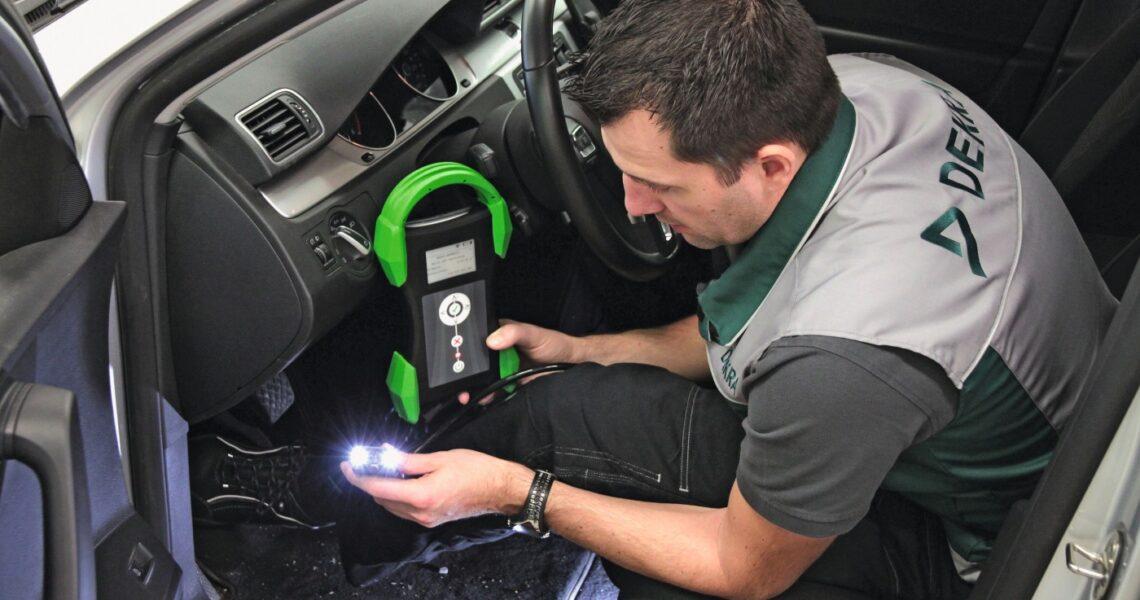 Dekra-Mitarbeiter steckt OBD-Adapter im Auto an