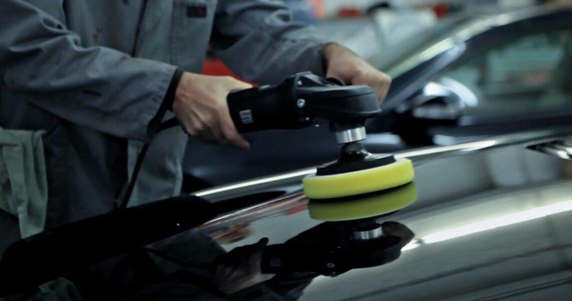 Ein Auto wird von einer Person mit einer Poliermaschine poliert